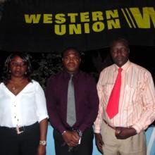 Steeve Armel MEMIAGHE (milieu), Philo Victor Nzolameso à sa guche et une employée de Western Union